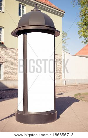 Mock up. Retro style street advertising column stand in the city at sunny day