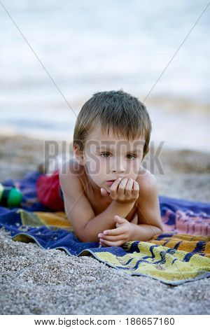 Portrait Of Cute Child, Boy, Contemplating The Beach, Lying Down On Towel