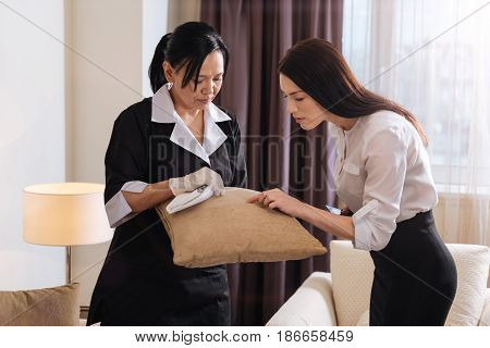 There is a spot here. Beautiful unhappy young woman looking at the cushion and pointing at the spot while talking to the hotel maid