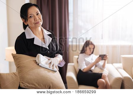 My work. Positive good looking hotel maid holding a cushion and smiling while cleaning it
