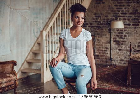 Beautiful african girl in white t-shirt sitting at home on a chair.