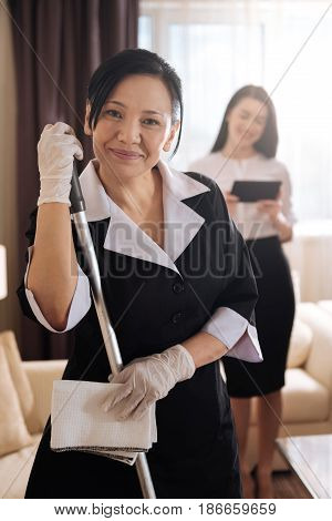 Everything is clean. Nice delighted hotel maid holding a mop and smiling while standing in the hotel room