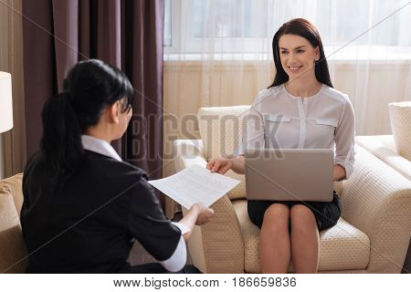 Your contract. Joyful pleasant professional manager holding a laptop and smiling while giving a hotel maid her working contract