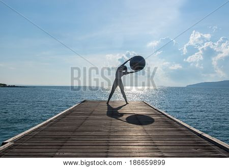 Yoga ball pilates ball young woman in the beach sunrise background