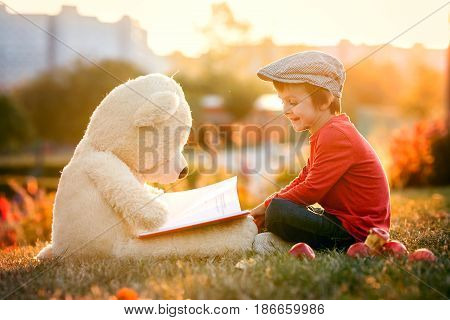 Adorable Little Boy With His Teddy Bear Friend In The Park On Sunset