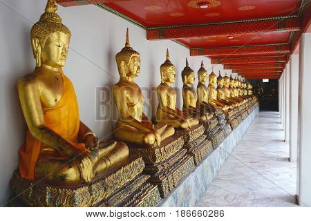 Row of golden Buddha statues in Wat Pho. Temple of the Reclining Buddha in Bangkok Thailand.
