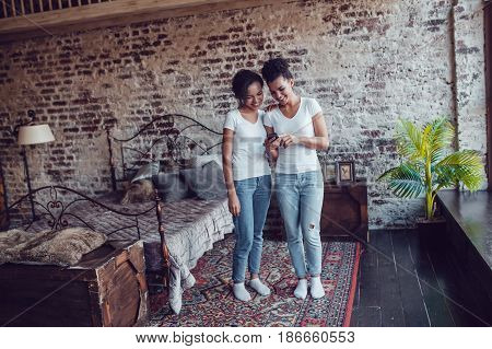 Two attractive African girls at home use smartphone.