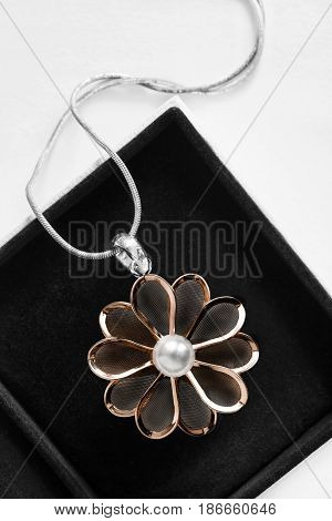 Golden flower pendant with one pearl in black jewel box closeup