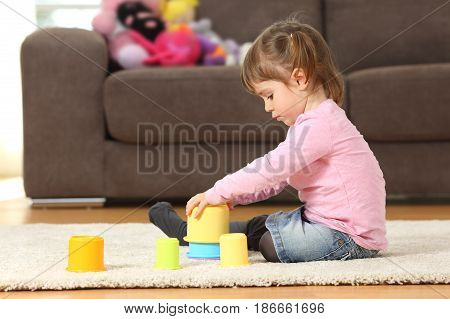 Side view of a kid playing with toys sitting on the floor of the living room at home