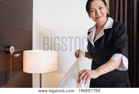 Service staff. Happy delighted Asian woman changing the bedding and looking at you while working as a hotel maid
