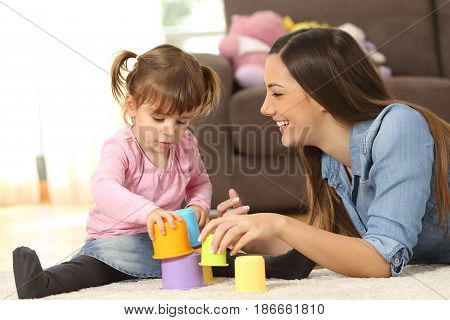 Happy mother and concentrated baby daughter playing with toys together sitting on the floor of the living room at home
