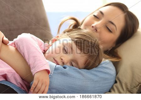 Close up of a mother embracing to her baby daughter and sleeping together lying on sofa at home with a warm light