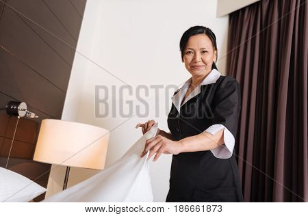 Positive mood. Nice pleasant professional hotel maid smiling and changing the bedding while enjoying her job