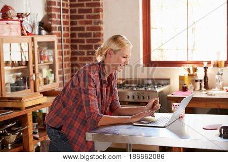 Young woman using computer in kitchen, waist up side view
