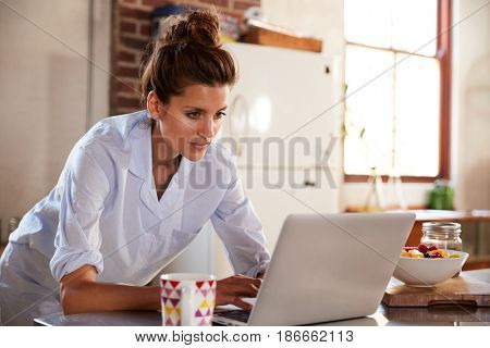 Young woman in pyjamas using laptop at breakfast, close up