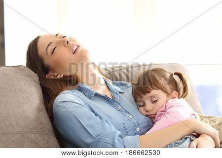 Tired mother sleeping embracing to her asleep baby daughter sitting on a sofa at home