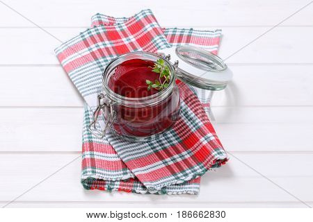 jar of thin beetroot slices on checkered dishtowel