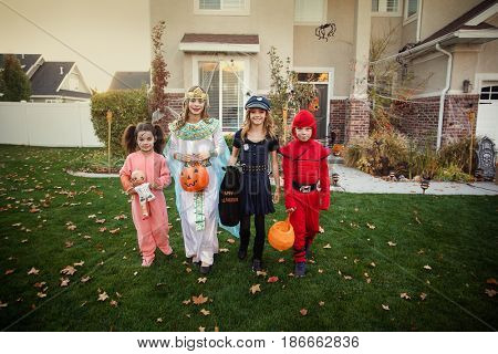Group of kids dressed in Halloween costumes going trick or treating outdoors in October in a residential neighborhood