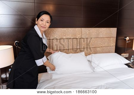 Almost ready. Good looking nice positive hotel maid holding a pillow and putting it on the bed while looking at you
