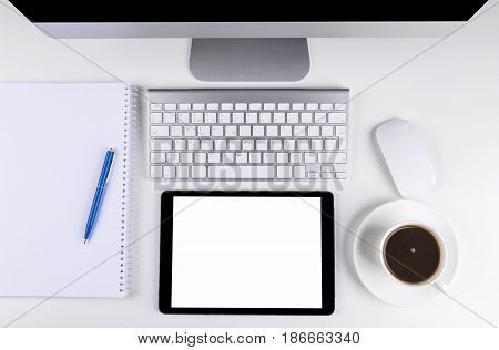 Office table with computer wireless computer keyboard and mouse cup of coffee tablet computer.copy space notebook. empty screen
