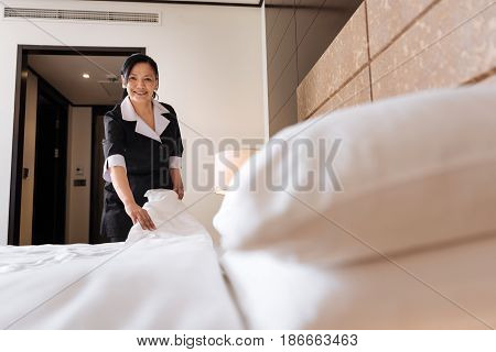 I like my job. Delighted nice professional hotel maid making the bed and smiling while enjoying her job