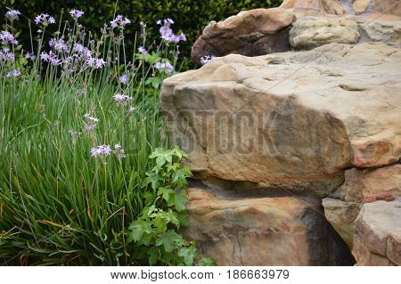 a pile of rocks with flowers in a garden