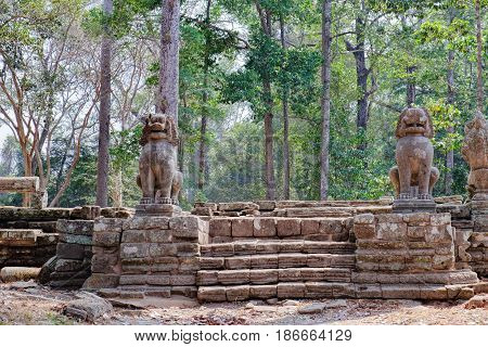 Lions in the foreground guard Prasat Bayon central temple of Angkor Thom, Siem Reap, Cambodia. Ancient Khmer architecture and famous Cambodian landmark, World Heritage.
