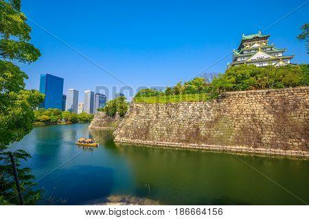 Wall and moat around Osaka Castle from Nishinomaru Garden and skyscrapers of Osaka Business Park on background. Osaka Castle is one of most famous landmarks of Japan and Osaka.