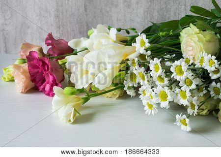A bouquet of white freesia, lisianthus, chrysanthemum and roses.