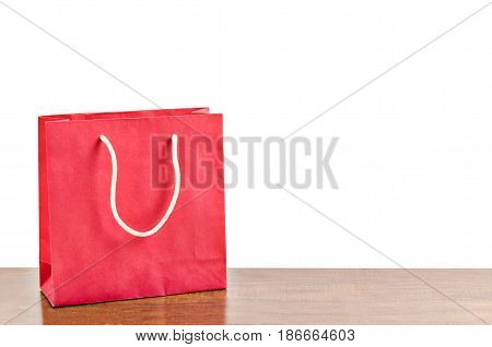 Red shopping bag on wooden table over white background. Save clipping path.