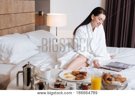 Before breakfast. Happy delighted attractive woman sitting on the bed and reading a magazine while waiting for her breakfast