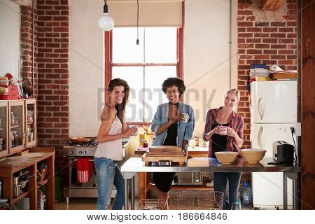 Three young adult girlfriends in kitchen look to camera