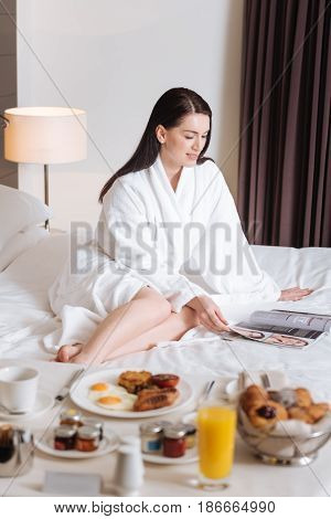 I am hungry. Nice attractive young woman wearing a bathrobe and turning over the magazine pages while waiting for her breakfast