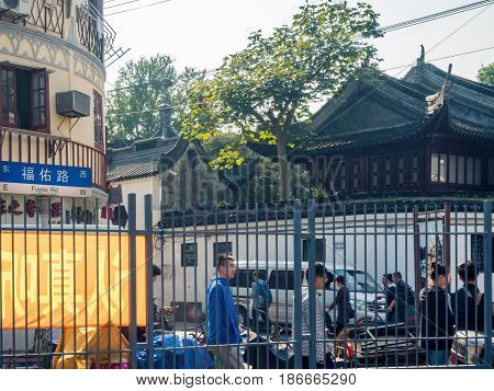 Shanghai, China - Nov 4, 2016: Fuyou Road - Overlooking the fence to a building with traditional Chinese architecture. Area bustling with people.