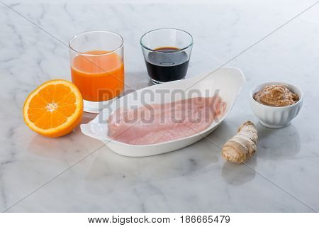 preparation for marinated chicken with orange juice soy sauce and ginger