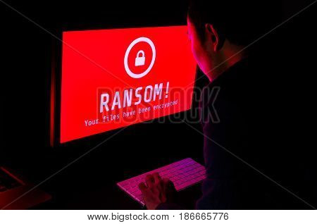 Computer screen with ransomware attack file encrypted alerts in red and a man in suit keying on keyboard in a dark room ideal for online security and digital crime