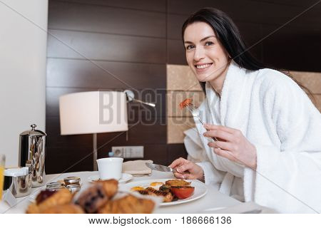 In the morning. Joyful happy positive woman holding a fork and taking a small piece of food while enjoying her breakfast