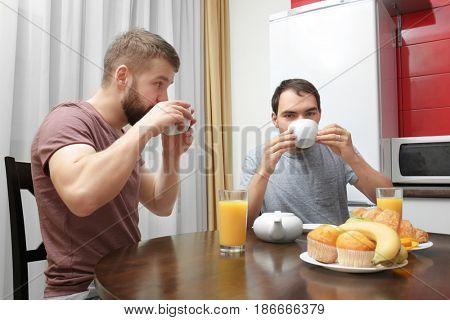 Gay couple having breakfast in kitchen