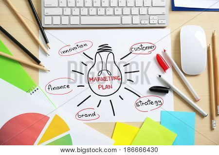 Paper sheet with text MARKETING PLAN on table