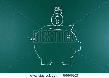 Chalk drawing of piggy bank on board