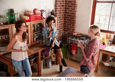 Three young adult girlfriends talk in kitchen, elevated view