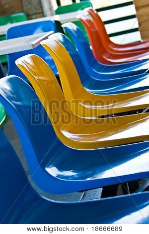 Multicolor plastic chairs in a kiddies restaurant poster