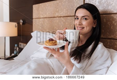 Wonderful breakfast. Nice positive delighted woman sitting in her bed and enjoying the tea while having breakfast