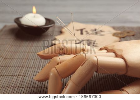 Model of hand with acupuncture needles on bamboo mat