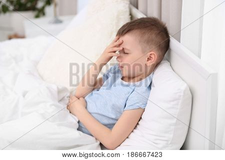 Little boy suffering from headache while lying in bed at home