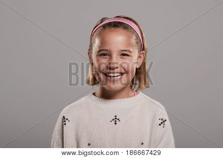 Nine year old girl smiling to camera, head and shoulders