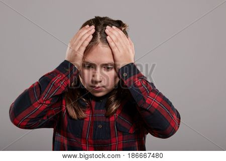 Ten year old girl holding head in confusion, waist up