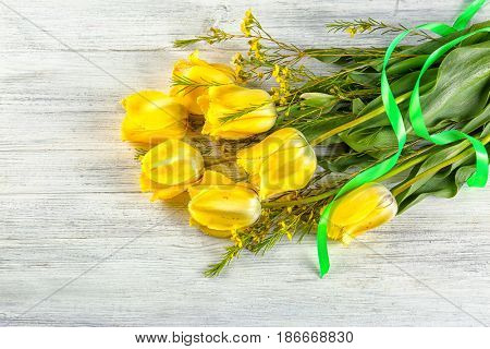 Bouquet of beautiful flowers on light wooden background