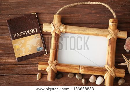 Travel concept. Bamboo frame with space for text, passport and cute decorations on wooden background