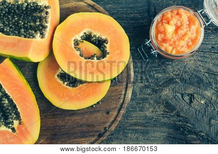 Fresh papaya natural facial mask peeling puree in glass jar on wooden background with place for text. Skin care and wellness vitamin antioxidant cosmetic concept. Top view. Copy space.